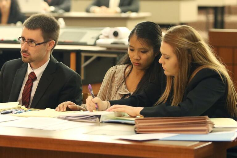 Three students pore over notes at a mock trial.