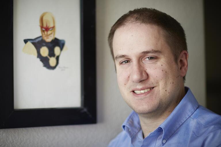man with superhero drawing on wall behind him