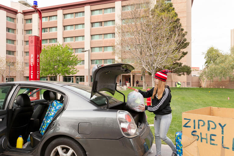 A student loads belongings into the back of her car