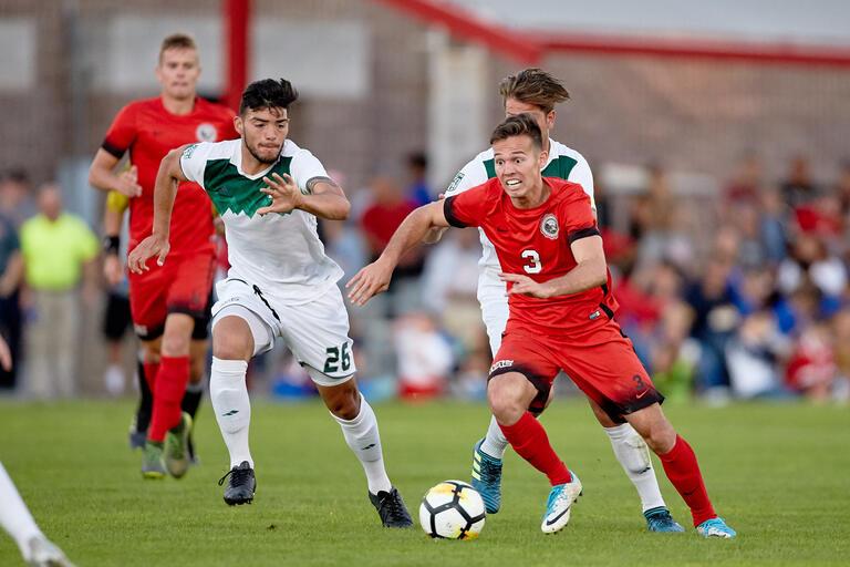 Danny Musovski dribbles a soccer ball