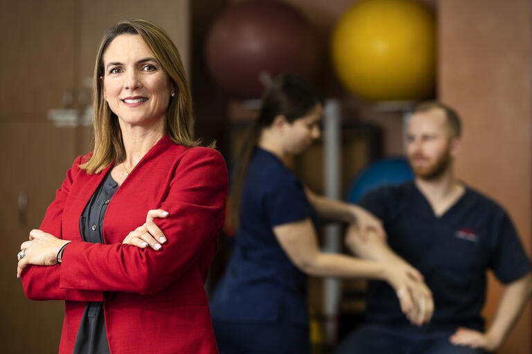 woman posing with two physical therapists working behind her