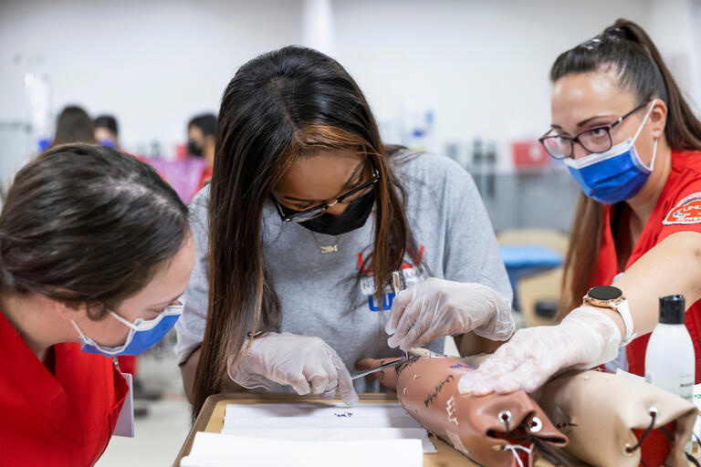 Three students work on removing sutures from a plastic arm