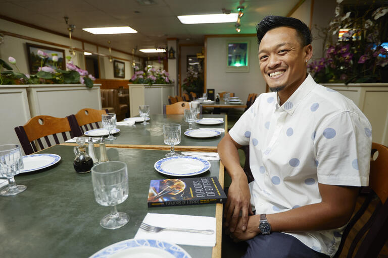 A man sits smiling at a restaurant table.