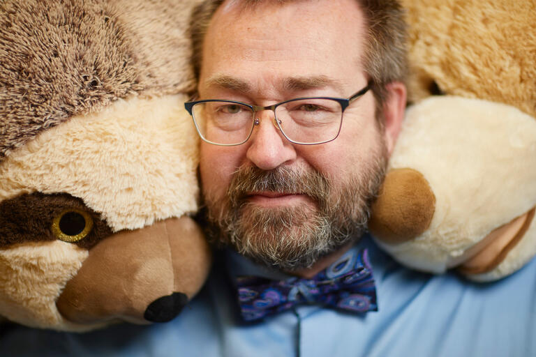 A close up of a man surrounded by stuffed animals
