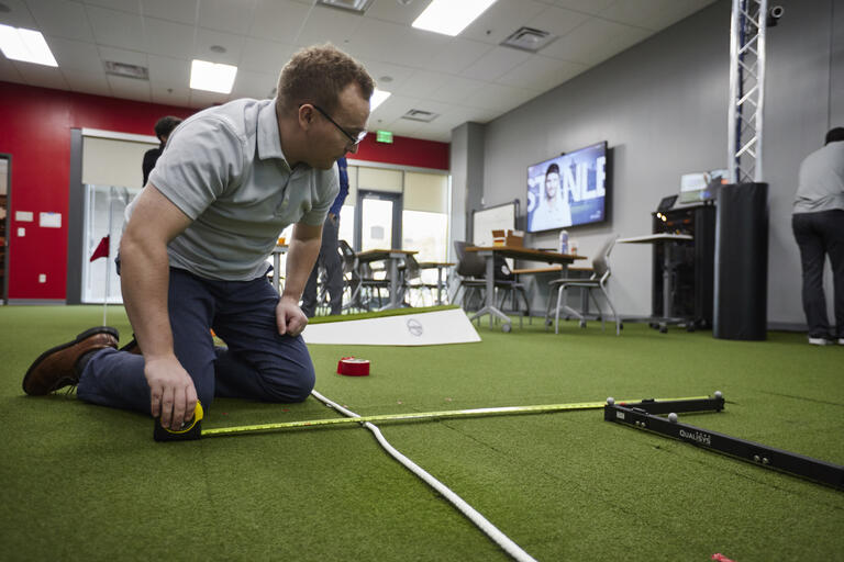 Samuel Masters uses a length of rope to measure out a distance on artificial grass.