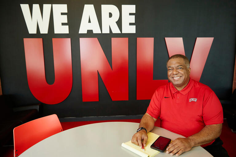 "A man sits at a tabel in front of a ""We Are UNLV"" sign"