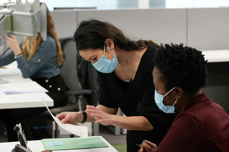 Two women wearing surgical masks look over paperwork