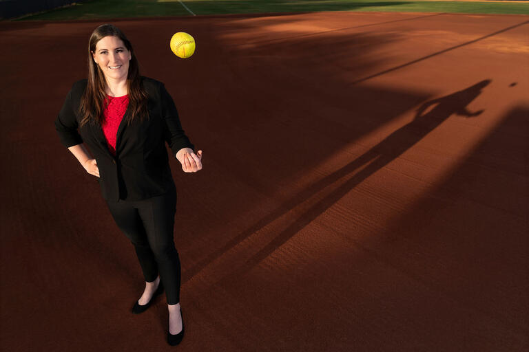 woman in suit tossing softball