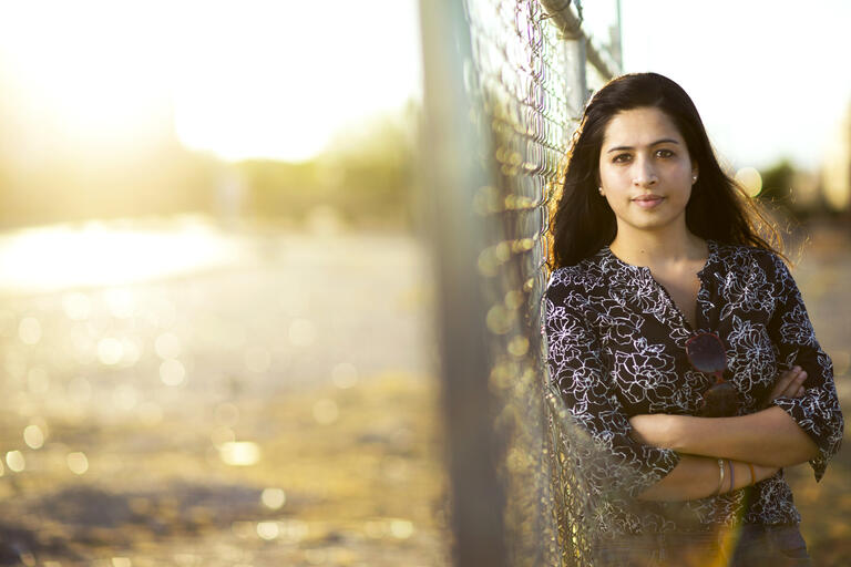 A woman leans against a chain-link fence as the sun sets in the background.