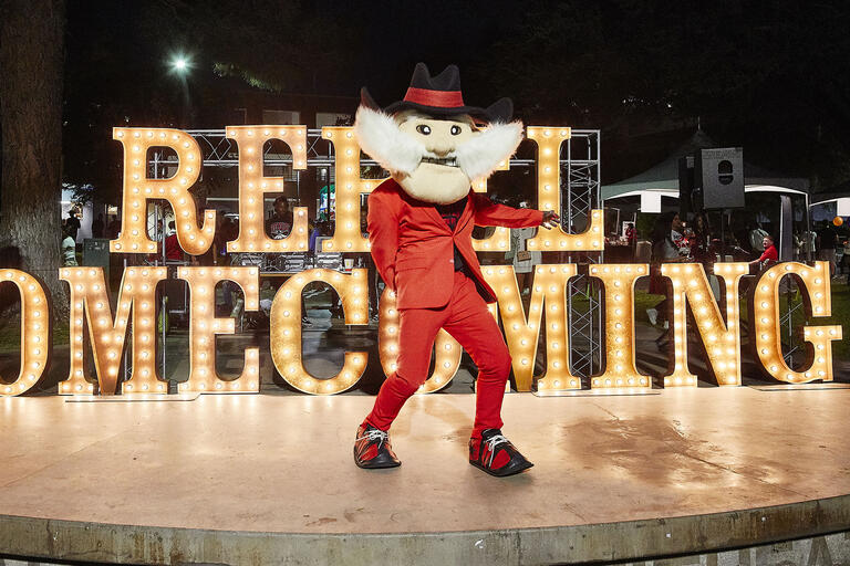 "Rebel mascot dancing in front of ""Rebel Homecoming"" sign"