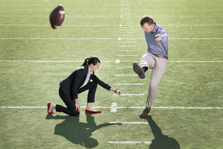 Evan Pantels kicks a football as Mallory Pool holds it.