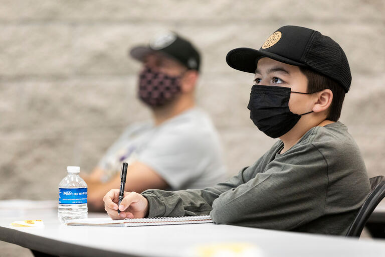 Young student wears a mask while taking notes in a classroom