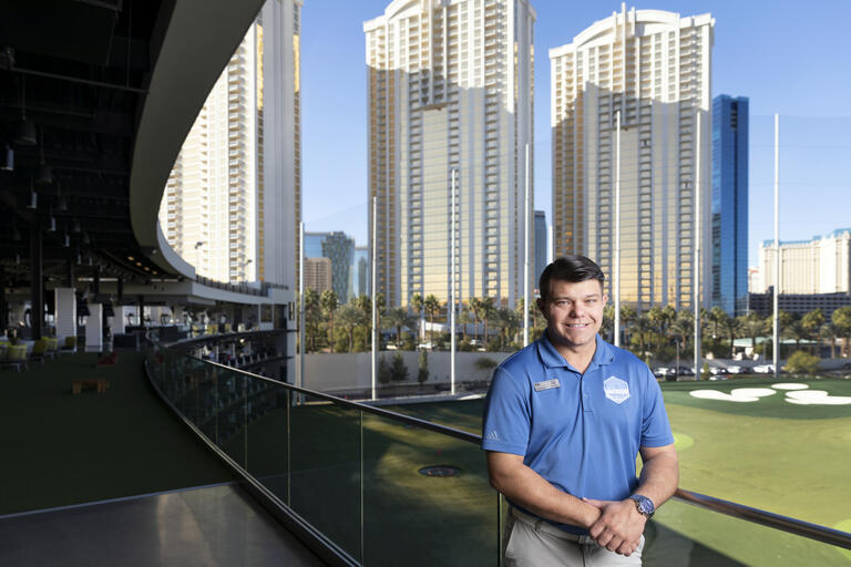Ryan Livermore stands in a Topgolf hitting bay