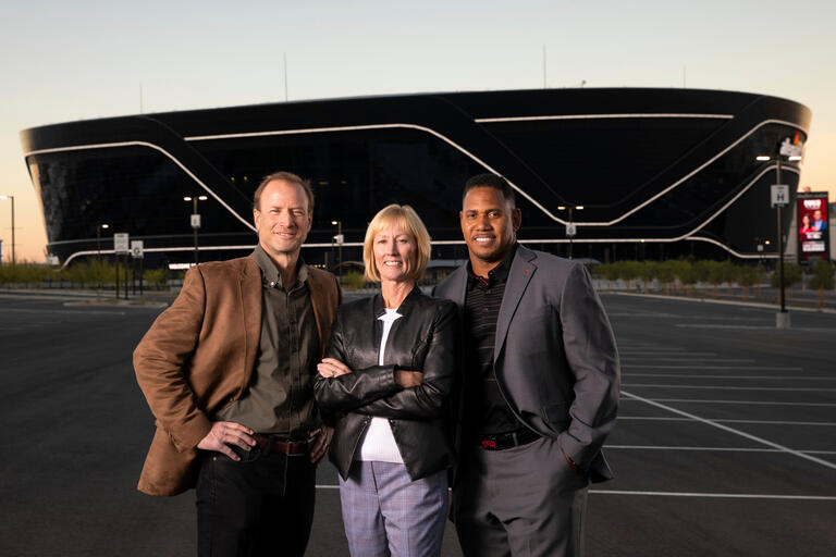 Three people stand framed by Allegiant Stadium in the background.