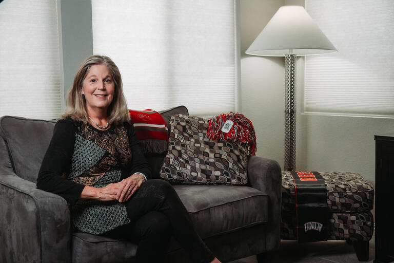 A woman sits on a couch, surrounded by UNLV paraphernalia