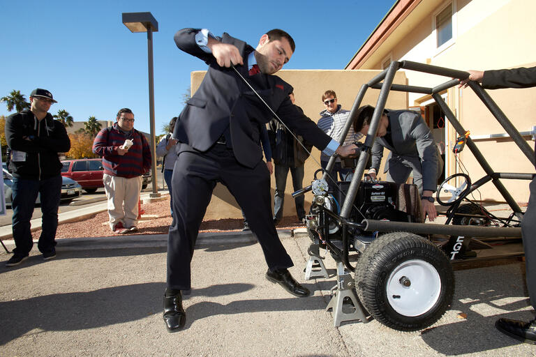A man in a suit pulls a cord on a dune buggy