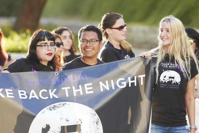 students hold up a take back the night banner