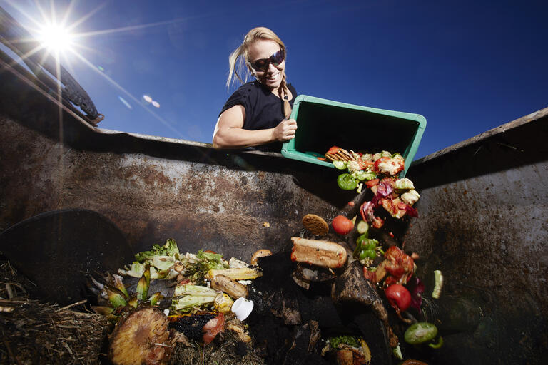 Tara Pike empties food material into UNLV's new composter.