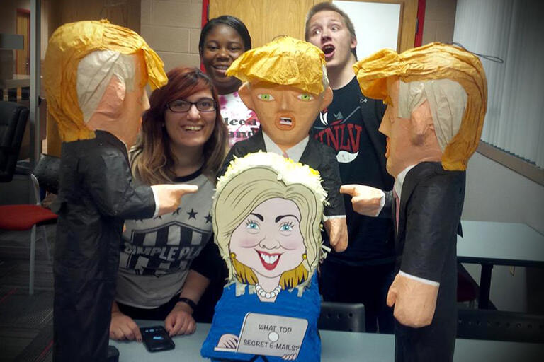 Students pose with Donald Trump and Hillary Clinton piñatas.