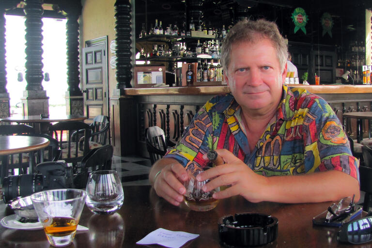 A man in a colorful shirt holds a cigar at a bar in Havana, Cuba.