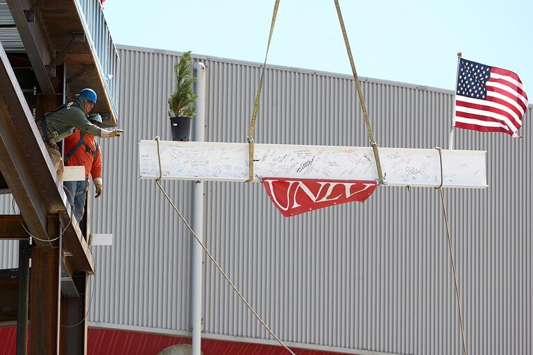 Construction workers guiding a beam up the side of a building.