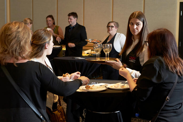 A group gathers and eats while a student serves wine from a tray