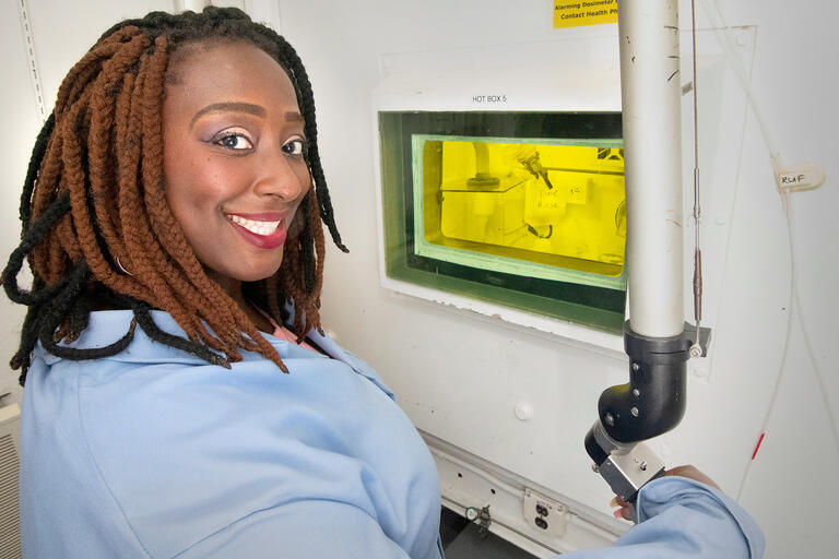 A woman smiles while working with scientific equipment