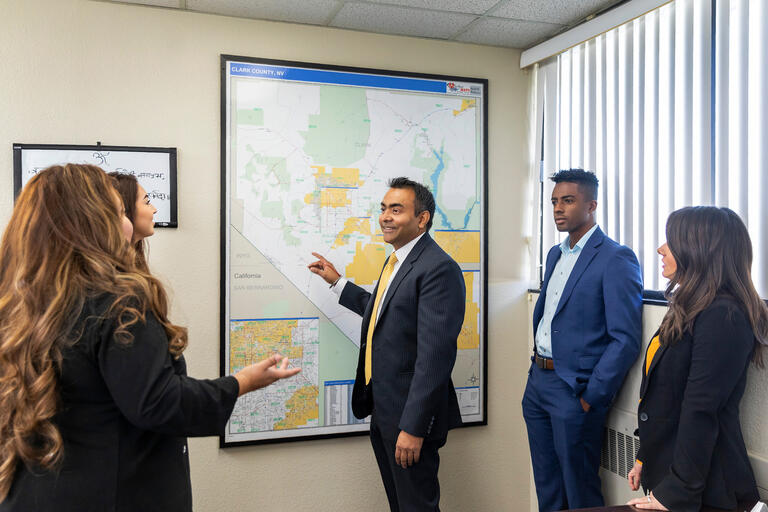 A man in a suit points to a map of Clark County as several students look on