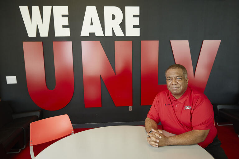"man sitting in front of display wall that says ""We Are UNLV"""
