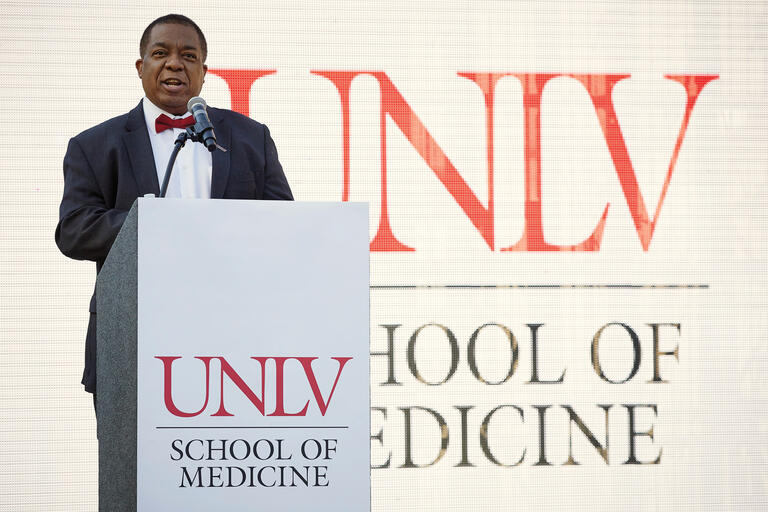 A man stands at a UNLV School of Medicine podium