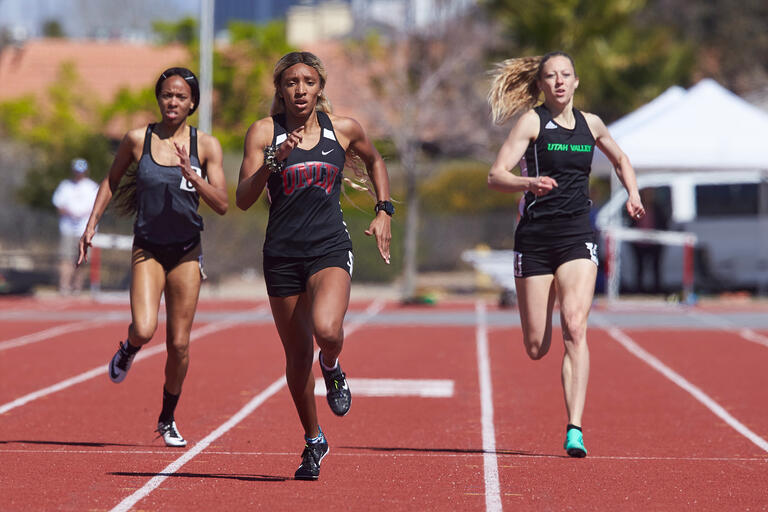 Three runners race down their lanes at a track meet.