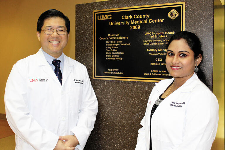 Drs. Ji Won Yoo and Ashley Sarasan pose in front of a plaque.
