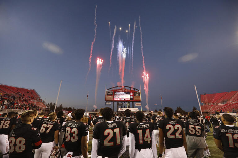 football players look up at fireworks display