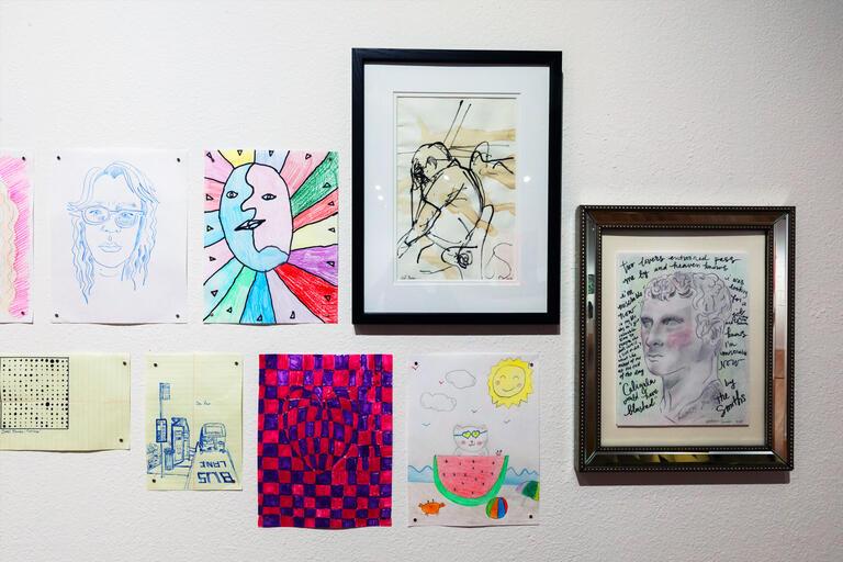 Several drawings hang on a wall