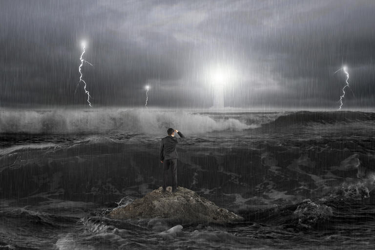 Man on rock gazing at lighthouse in the ocean with storm, thunder, lightening and waves in dark