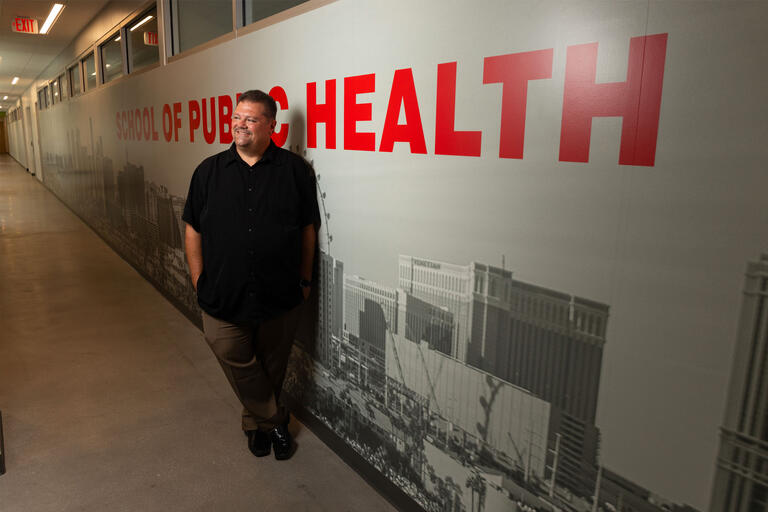 """A man stands in front of a wall that reads """"School of Public health"""""""