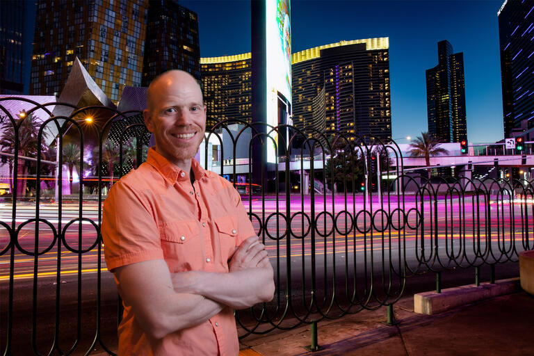 A man stands in front of the Las Vegas Strip at dusk