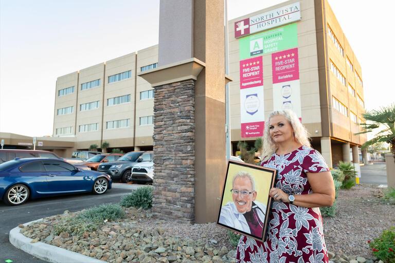 A woman holds a portrait outside a hospital
