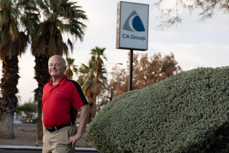 A man stands in front of a sign for the CA Group