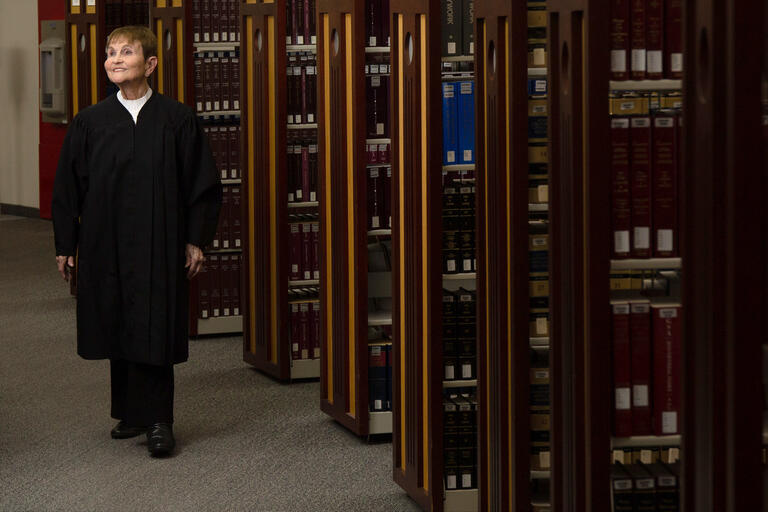 A woman in judge's robes walks through the stacks of a law library