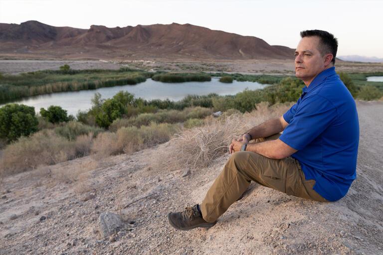 A man sits on a hill near a stream