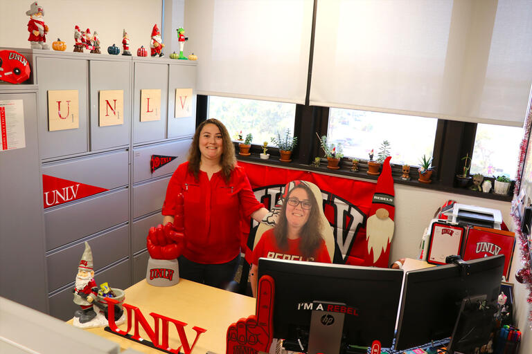 A woman stands in her office surrounded by UNLV memorabilia