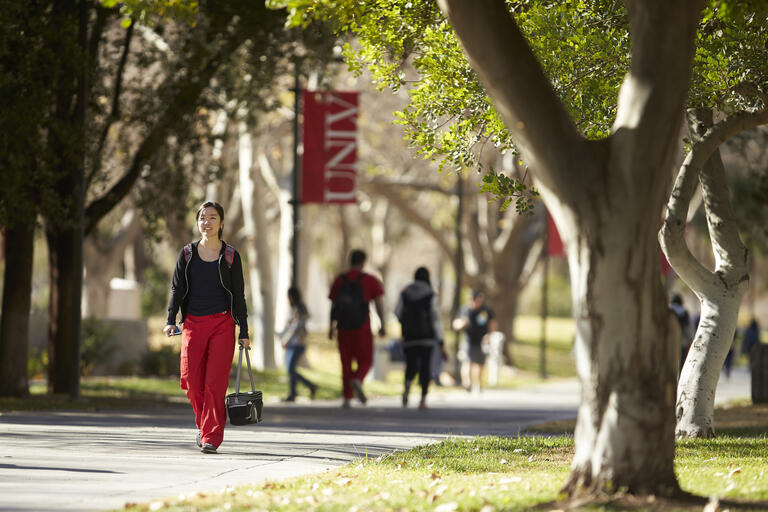 Female student walking on campus during a sunny day.