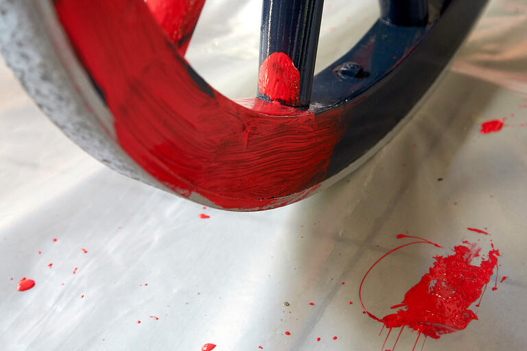 A  blue cannon wheel being painted red.