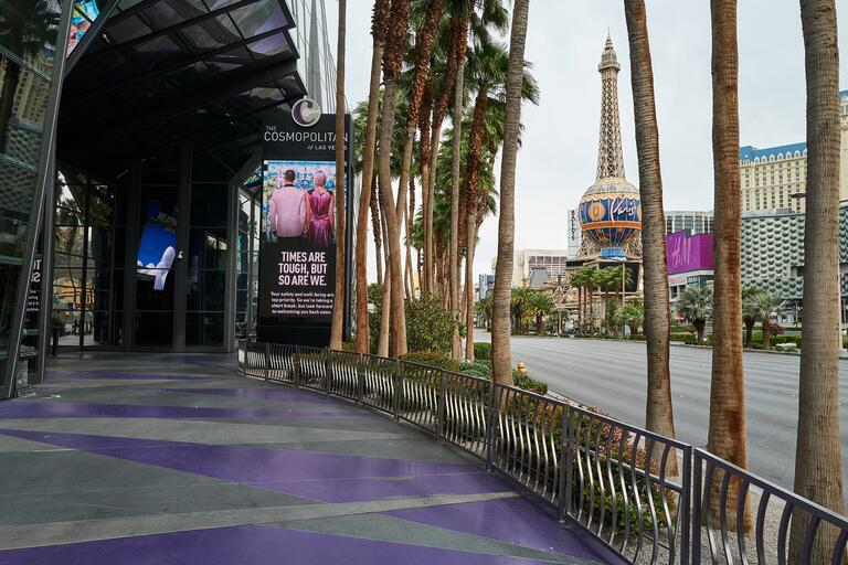 View of empty Vegas Strip walkway with sign that says: Times are tough, but so are we.