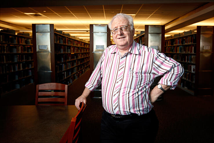 Professor Eugene Moehring standing in the library