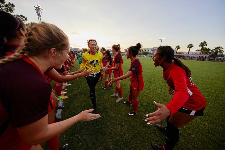 Emberly in her goalkeeper uniform runs through a line of fellow soccer players giving high-fives.