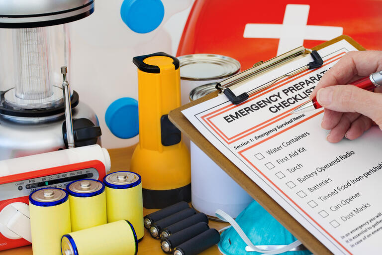 items from an emergency kit: batteries, flashlight, first aid kit