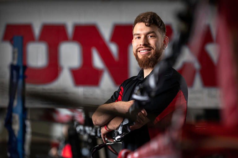 """A student poses in a boxing ring with """"UNLV"""" letters drawn on the wall behind him."""