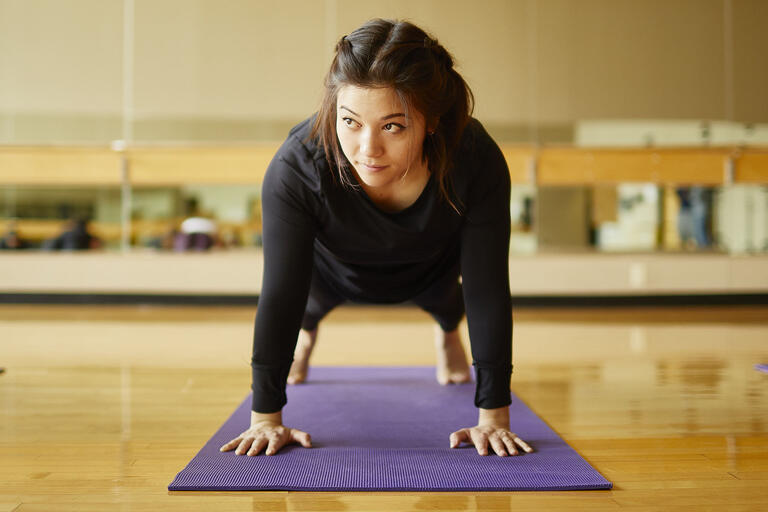 woman doing a plank on yoga mat